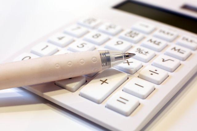 テーブルの上に置かれたノートとペンと電卓